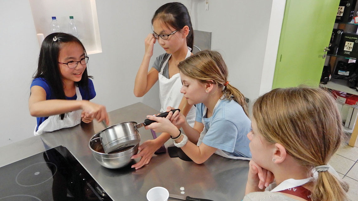 The author's twin daughters, on right, make friends and macarons during a class at Cuisine Aptitude in Strasbourg, France.