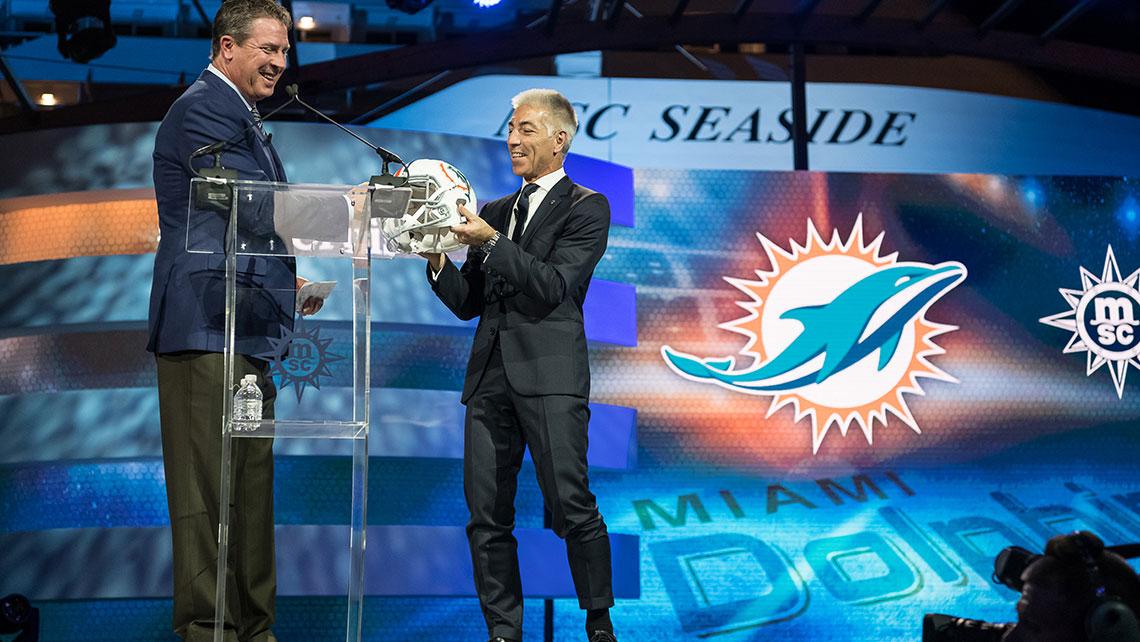 Dan Marino gives a Miami Dolphins helmet to MSC Cruises USA President Roberto Fusaro. Photo Credit: Ivan Sarfatti
