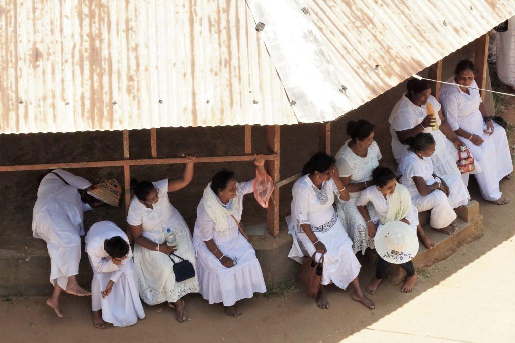 Sri lankaanse pelgrims rusten uit in de zon