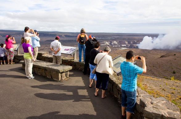 Visitors gather at Kilauea Overlook, adjacent the Jaggar Museum, to observe volcanic gases billowing from Halema'uma'u Crater, the most active point within Kilauea's summit caldera, Big Island, Hawaii. Photo by Dave Houser.