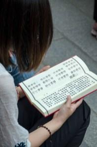TiawanTemples-woman reading prayer book