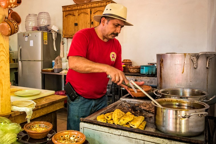Chef and owner Enrique Robles making tacos at Birrierias Robles restaurant, on the El Pitillal Food Tour with Vallarta Food Tours; Puerto Vallarta, Mexico.