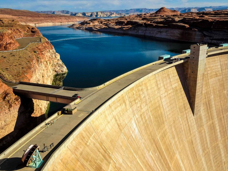 """Glen Canyon Dam - The second largest dam in the US, only 16 feet shorter than Hoover Dam, is the reason why the Colorado River is no longer """"colorado"""" (red), the dam filters out the natural, red sediment in the water. Projects are underway to allow the dam to more naturally mimic its ancient flow."""