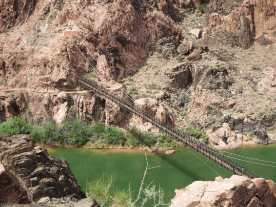 A suspension bridge provides the means for hikers to cross the Colorado River at the bottom of the canyon.