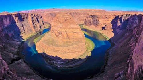 Horseshoe Bend, located within the Glen Canyon National Recreation Area, is accessible via a 1.25 mile roundtrip hike from the trailhead parking lot