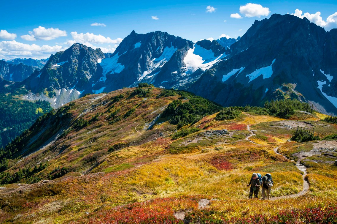 Couple with backpacks hiking on Sahale Arm Trail, Cascade Pass, North Cascades National Park, Washington.