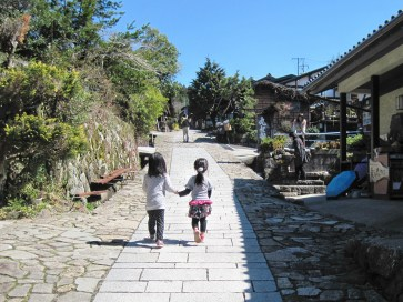Two little girls walk uphill on the stone-paved main street of one of the small villages along Japan's Nakasendo Way. Photo by Peter Mandel