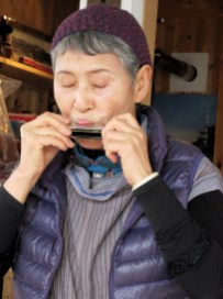 Mitsuko Ando plays the harmonica for guests at Kaida-no Poppo-ya, a tiny Italian-Japanese restaurant in Nagano, Japan, that she owns along with her husband. Photo by Peter Mandel