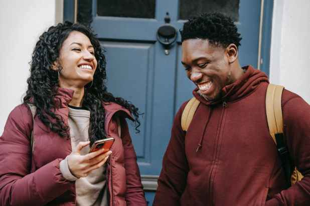 diverse cheerful friends with smartphone laughing near door of building