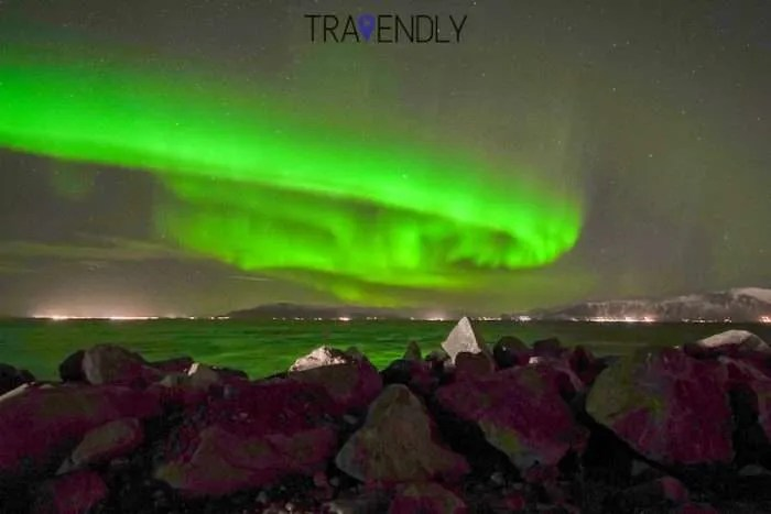 Northern Lights swirl over the ocean in Iceland
