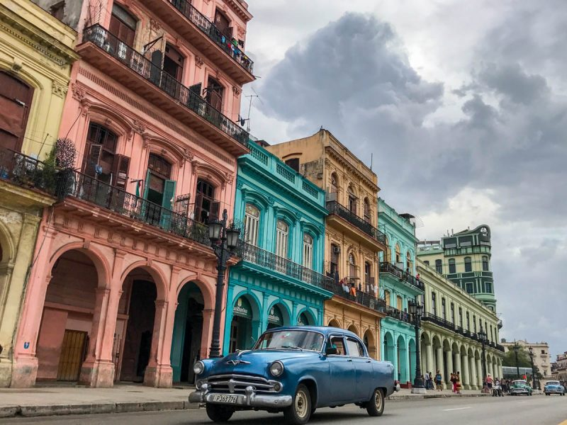 Classic car driving by colorful buildings in Havana