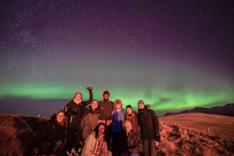 Group in field under the Northern Lights