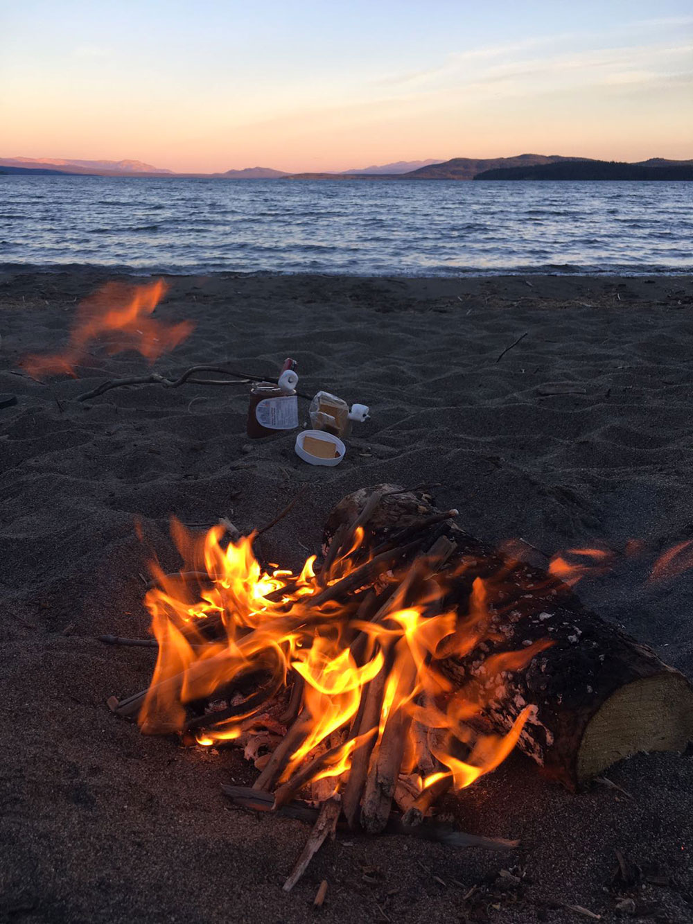 Feu de camp et marshmallows au bord d'un lac
