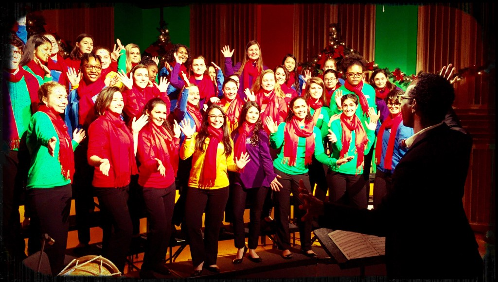 The Boston Children's Chorus wearing colorful T-Shirts and red scarves standing Frasier Studio smiling with hands up.