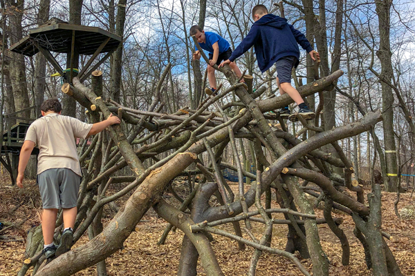 Boys Climbing on Wood Structure