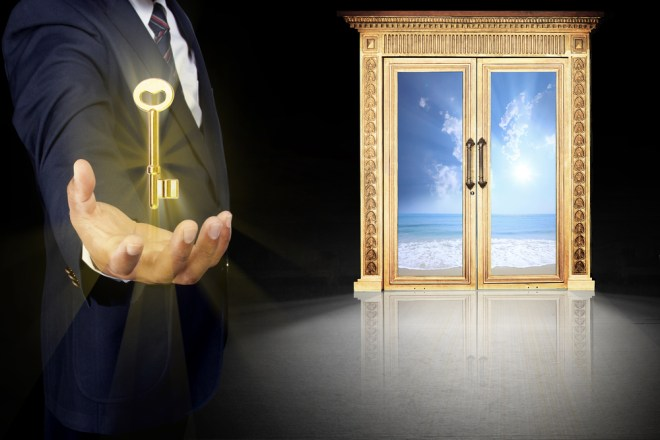 A man holds out a glowing key in front of golden doors