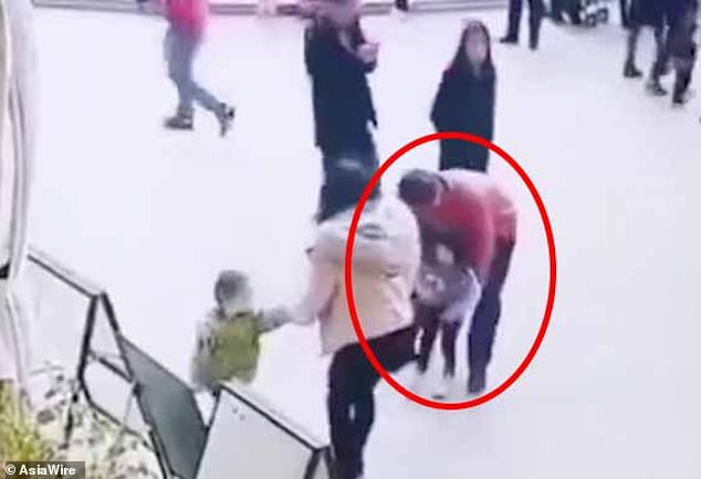 A man has been detained by police after he had attempted to snatch a two-year-old girl (circled) from her aunt at a shopping mall in Shenzhen, south-east China