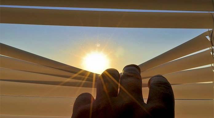 promienie słoneczne wpadające przez roletę