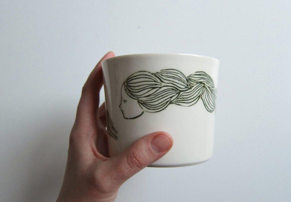 Tasse de porcelaine blanche à la main unique avec une illustration de la jeune fille aux longs cheveux, pour toutes sortes de boissons, des desserts et des collations.