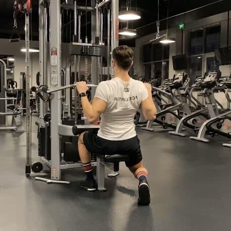 Osobný fitness tréner ukazujúci ako trénovať príťahy na chrbát kvalitne a bezpečne