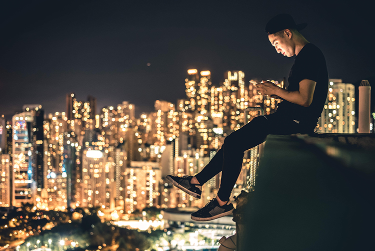 man sitting on ledge on cell phone city skyline behind