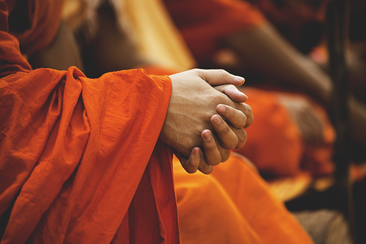 monk in orange robes with praying hands
