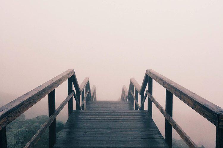wooden walkway through thick fog