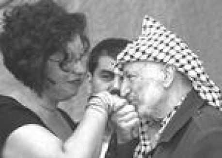 Palestinian leader Yasser Arafat kisses the hand of an unidentified member of a delegation of representatives of international communist organizations that visited him at his headquarters in the West Bank city of Ramallah, Sunday Oct. 13, 2002. (AP Photo/Vadim Ghirda)