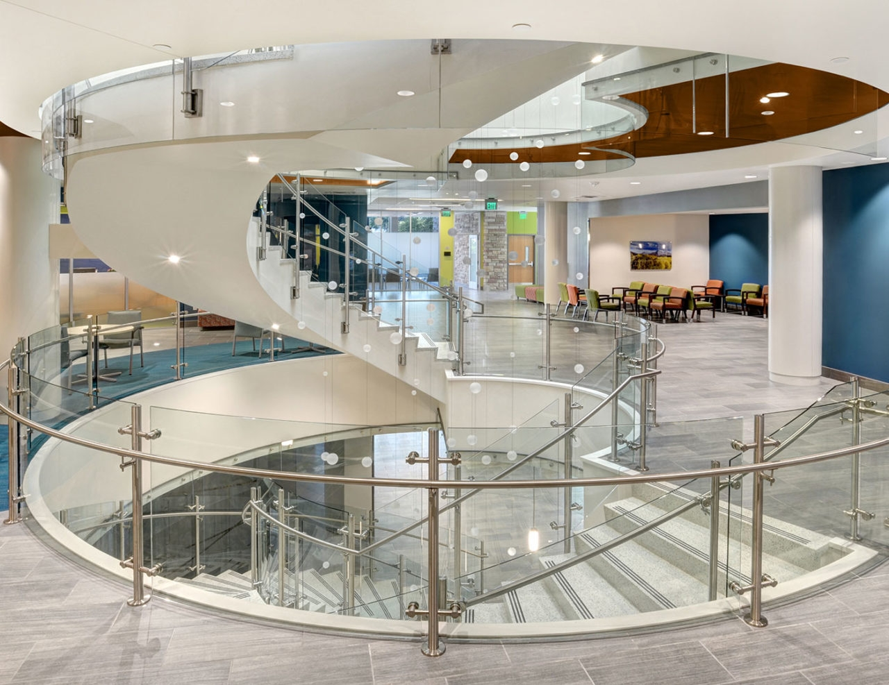 Equinox Glass Railing System Trex Commercial Products | Staircase Design For Commercial Buildings | Cylindrical Glass | Enclosed | Beautiful | Central Staircase | Sleek