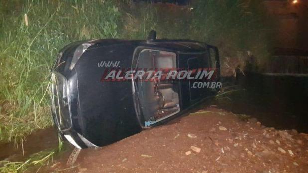 Condutor cai com carro dentro de córrego no Centro de Rolim de Moura