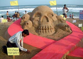 Renowned sand artist Sudarshan Patnaik creates a symbolic gesture during an HIV/AIDS awareness campaign