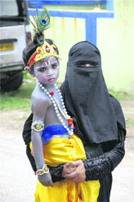 A Muslim woman carries her son, dressed as Lord Krishna, for a school function to celebrate Janmashtami, in Patna on Wednesday.