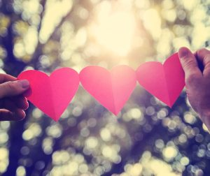 hands holding a string of paper hearts up to the sun during suns