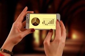 Foto de mulher olhando para a tela do celular que mostra gráficos financeiros realocação de ativos como fazemos
