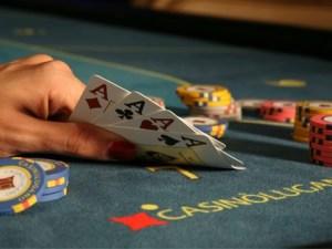Imagem de jogador de poker com quadra de ases na mão em um Cassino Alocação de Ativos