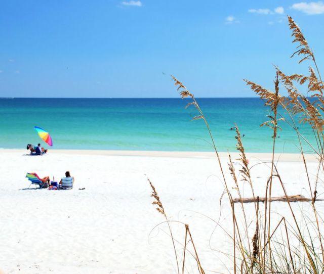 Beachgoers Enjoying White Sand And Emerald Water Of Destin Florida