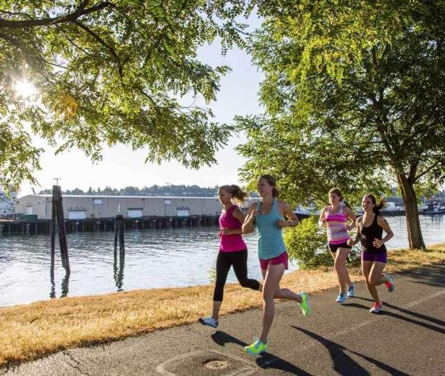 Four Young Women Jogging Together Along Coastal Park Seattle Washington Usa