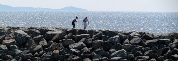 At the harbor in Riviere Du Loup waiting for the ferry I see a couple playing on the rocks.