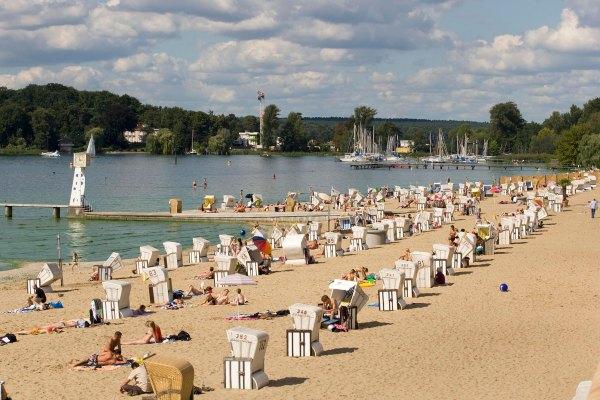 Pieniä istumakoppeja pitkällä hiekkaisella uimarannalla