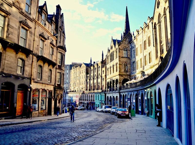 Man walking down cobbled Edinburgh street