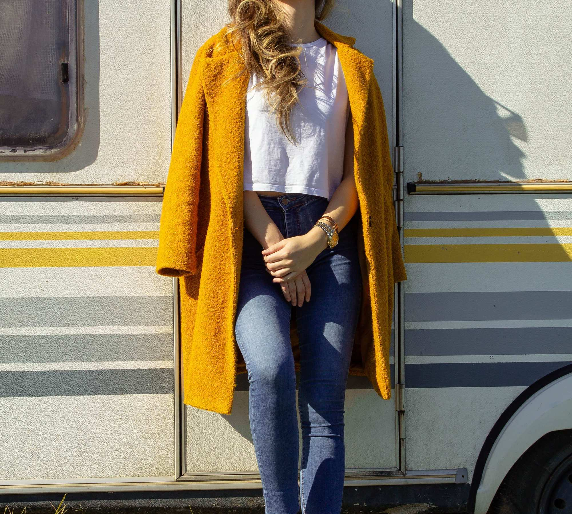 woman in front of yellow travel trailer