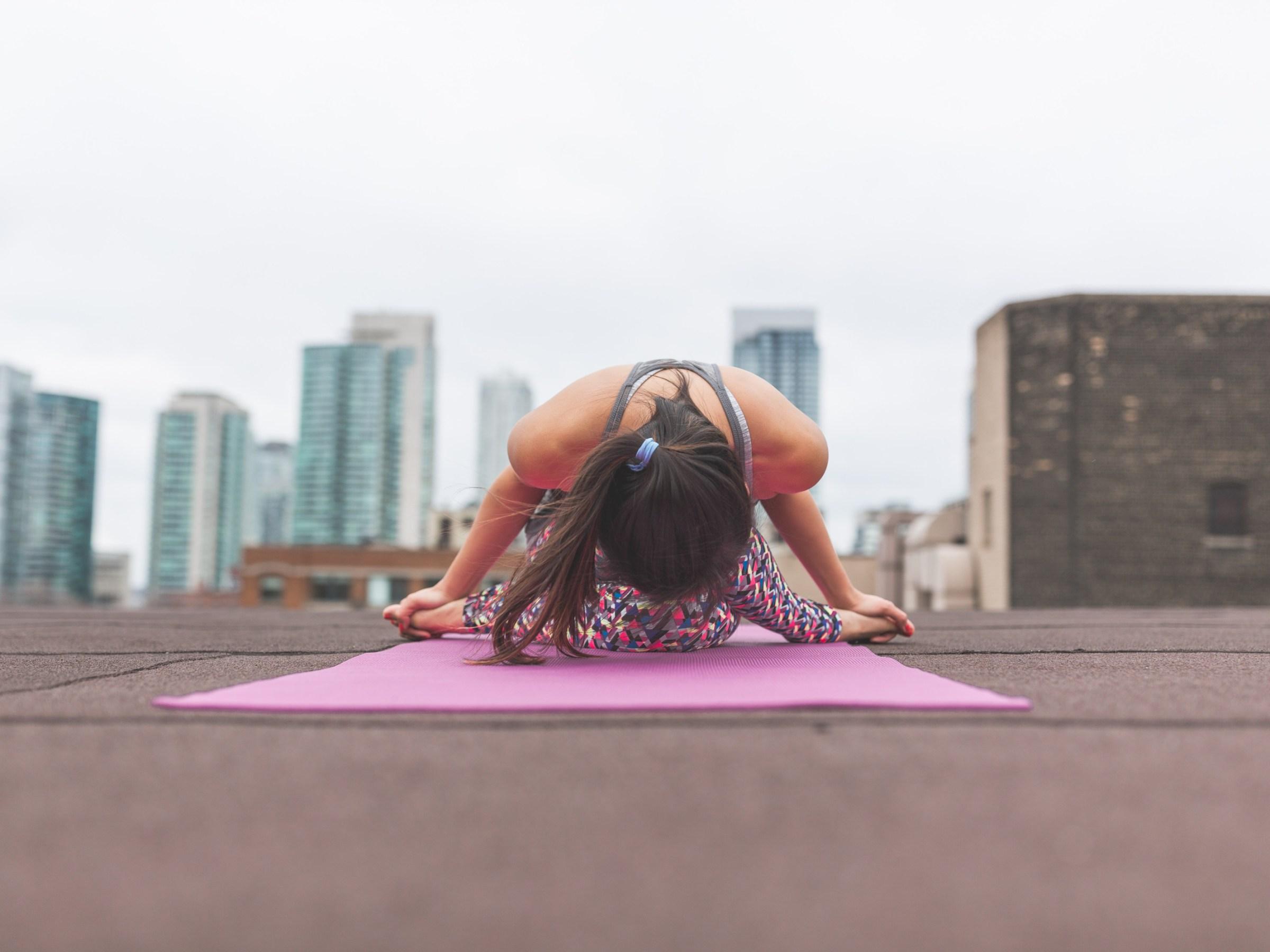 radical self-care : woman doing yoga bow to city