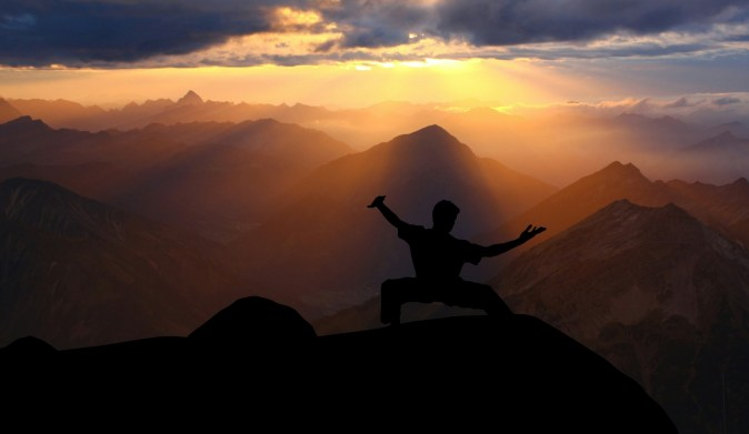 easy meditation online / self-care pic: silhouette of man doing tai chi on a cliff at sunset