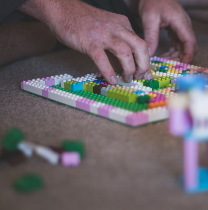 sobriety and relapse pic: person building structure foundation with lego blocks