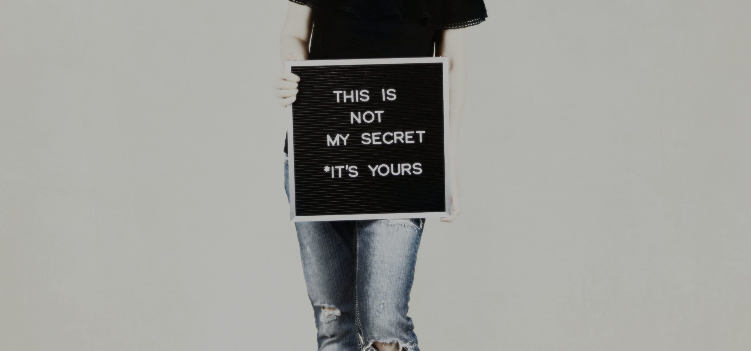 "woman holding sign reading ""this is not my secret; it's yours"""