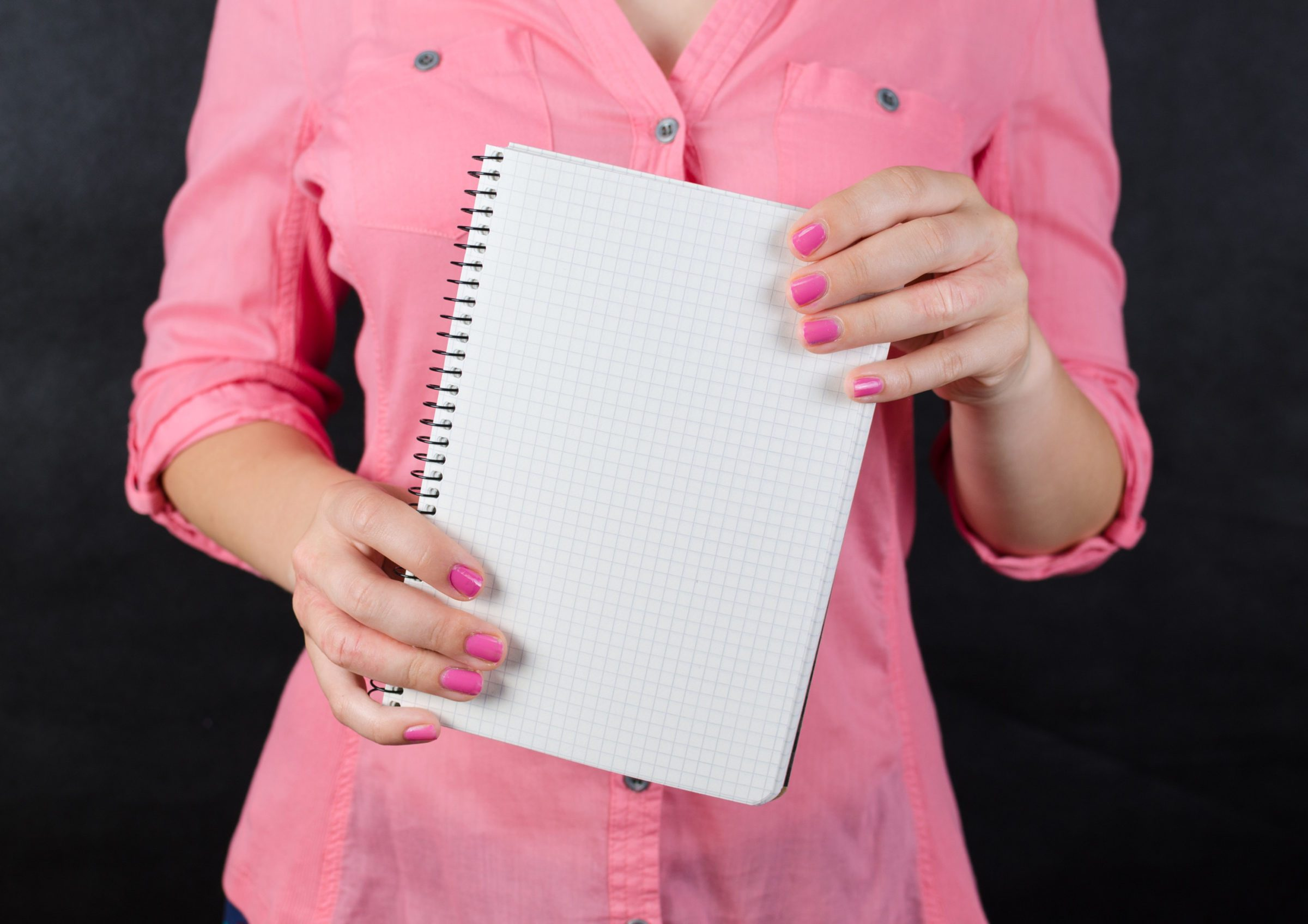 woman in pink shirt holding spiral notebook