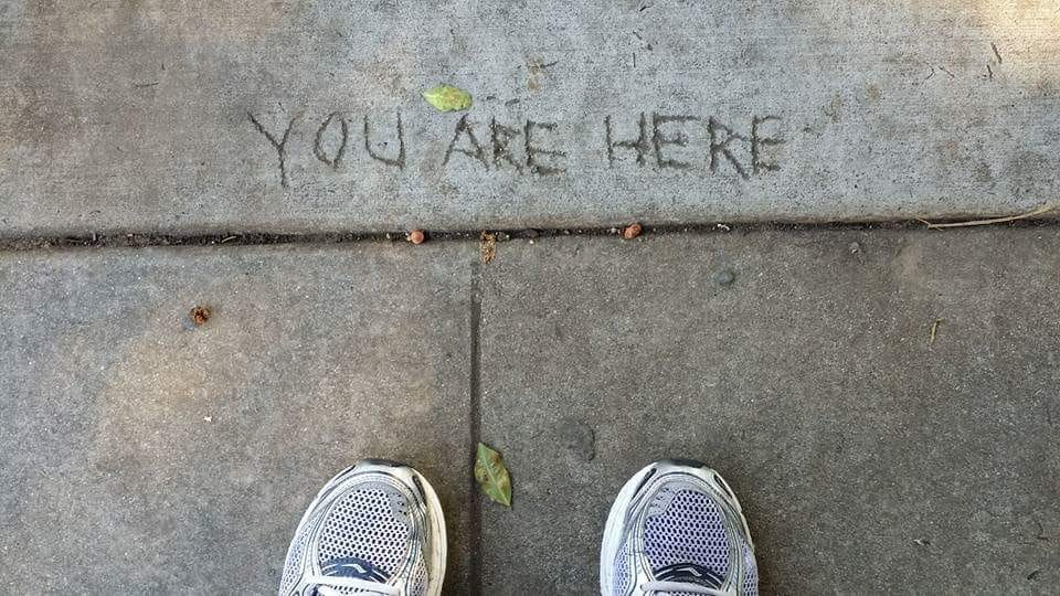 "sidewalk etching of the words ""you are here"""