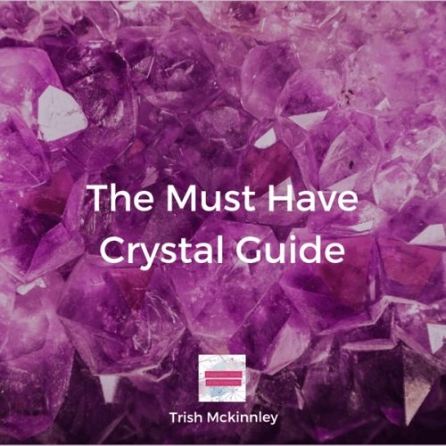 Close-up of purple crystals with 'The Must Have Crystal Guide' written over it