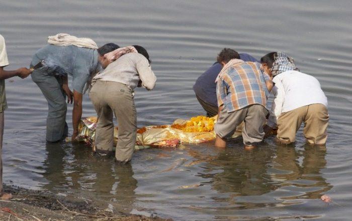 FAMILIARES PURIFICANDO UN CADAVER EN EL RÍO GANGES EN EL GHAT DE HARISCHANDRA EN VARANASI
