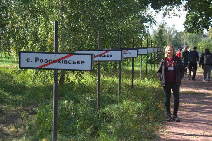 BEATRIZ EN EL MEMORIAL CAMINO CON LAS PLACAS DE LAS LOCALIDADES AFECTADAS DENTRO DE LA ZONA DE EXCLUSIÓN EN CHERNOBYL